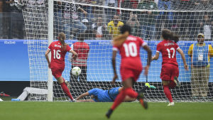Kanadas Janine Beckie lägger bollen i mål bakom den australiensiska målvakten.