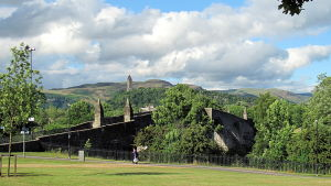 En gammal stenbro i grönt landskap: Stirling Bridge. William Wallace-monument i bakrgunden.