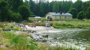 badstrand och gult hus på sommaren