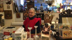 Ritva Blomqvist står i sin antikaffär iklädd en röd klänning.
