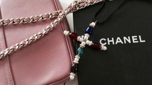 En rosafärgad handväska och ett smycke med ädelstensfärgade kulor som bildar ett kors.