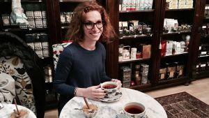 Olga Liebkind sitter och dricker te på ett tehus i Helsingfors.