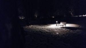 en ensam parkbänk i mörkret