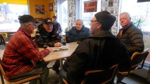 Ett sällskap äldre män runt ett cafébord.