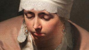 En kvinna med spetsduk runt huvudet och caméörhängen i öronen.