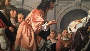 Människor i 1600-tals kläder möts i en festsal.