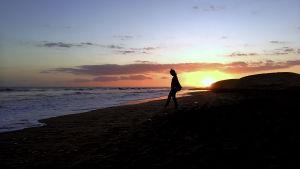 nainen meren rannalla auringon laskiessa