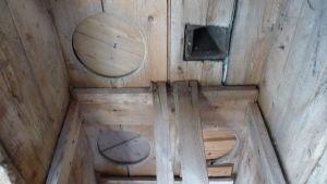 ett gammalt innertak i trä  där man kan se de intäckta gamla hålen från ett utedass.