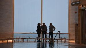 Tre personer i motljus mot ett stort fönsterglas, vid en bassäng.