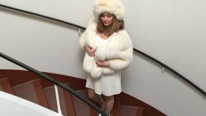 Emma Sandström står i en trappa i klädd vit pälsmössa, vit päls och klänning.