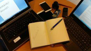 Datorer, telefoner, en padda och ett skrivhäfte ligger på ett bord.