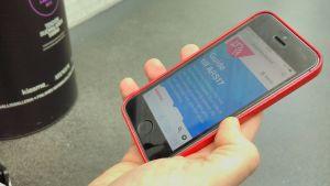 En hand som håller i en telefon där ARS17-mobilguiden syns på displayen.