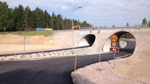 En nybyggd järnvägsundergång för bilar och lätt trafik i Svedja i Karis. Också män i arbetskläder syns på bilden.