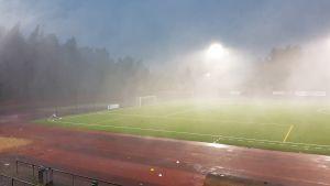 Det regnar hårt på fotbollsplanen.