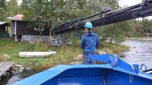 Lyftanordning på väg att gripa tag om en gammal roddbåt.