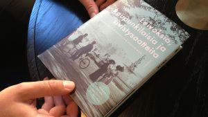 Samu Nyström visar upp jubileumsboken till professor Laura Kolbes ära. Han är en av de tre redaktörer som hållit i projektet.