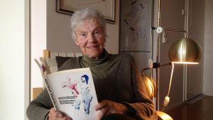Märta Tikkanen sitter med boken Århundradets kärlekssaga i famnen