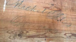 ett namn skrivet på baksidan av ett skrivbord