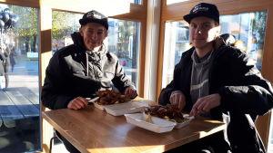 Två ungdomar sitter och äter kebab vid en kebabrestaurang på Brändö i Vasa.