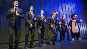 Sex män i kostym och en man utklädd till pingvin på en scen