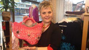 kvinna i butik visar upp väska som liknar sko