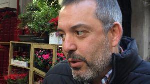 Självständighetsivraren Francisco sitter framför en hylla med blommor.