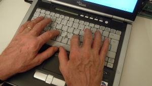 kädet kannetavan tietokoneen näppäimistöllä