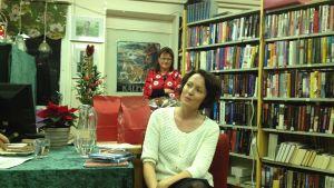 Två kvinnor framför bokhyllor, den ena sitter och den andra står bakom. Till vänster syns ett bord med grön duk, i bakgrunden en julgran.