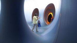 En man i gul skjorta spelar flöjt i Colourscape, ett konstverk man kan gå in i och genom runda gångar.