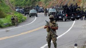Beväpnade poliser vid parkerade bilar.