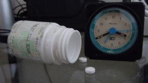 Burk med medicin invid en väckaklocka.