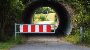 Vägspärr under rund tunnel