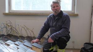 Tom Lindgren knäböjer framför omålade fågelholkar. Inomhus, ett fönster bakom. .