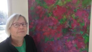 Pirjo Rautio framför en röd-lila rosenmålning i Ilmari Rautios ateljé i Simolan rosario i Klövskog, Nurmijärvi. 2017.