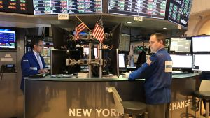 Två aktiemäklare har dekorerat sin runda desk med amerikanska flaggor, vid börsen i New York.