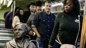 Figuren som föreställer Rosa Parks sitter i bussen på en vit plats. Nyfiken publik passerar