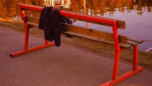Rannalla tyhjä puninen puistonpenkki ja sillä hetkeksi jätetty pusero; keväinen ilta-aurinko paistaapi.