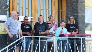 En bild på glada människor i centrum av Karis. De står på en trappa och en av personerna håller tal.