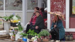 Många säljer en del av sin skörd på marknadsplatser. tre äldre kvinnor säljer olika grödor. En sitter under ett paraply.