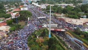Bild tagen uppofrån av en folkmassa kring en vägbro klädd i Nicaraguas vita och blåa färger.