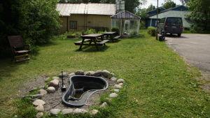 en trädgård med ett växthus och terassbord