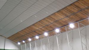 Tak som är välvt och vita väggar inne i en nysanerad tennishall.