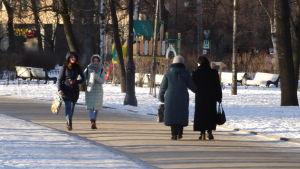 Kvinnor som går på en gata i ett snöigt Ryssland.