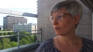 Kirsi Pimiä i profil på taket till DO:s byrå, betonghöghus i bakgrunden
