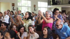 Församlingsmedlemmar stiger upp och hurrar under Silvio Báezs predikan.