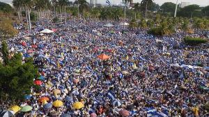 Stora blå-vitlädda folkmassor samlas för att protestera.
