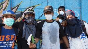 Unga maskerade män posterar framför en vägg med en molotov-cocktail i handen.