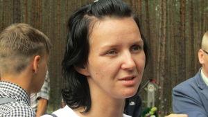 Katja Klodt, en svarthårig kvinna i vit t-tröja, tittar förbi kameran med fundersam blick.