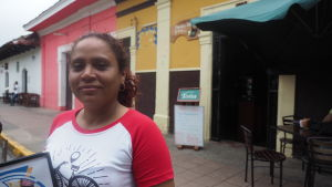 Yohanna Guadamus, en kvinna i medelåldern klädd i röd vit t-skjorta står framför en tom uteservering med en meny i handen.