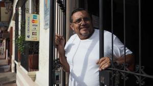 En rundlagd man i medelåldern tittar leende ut genom en gallerport.